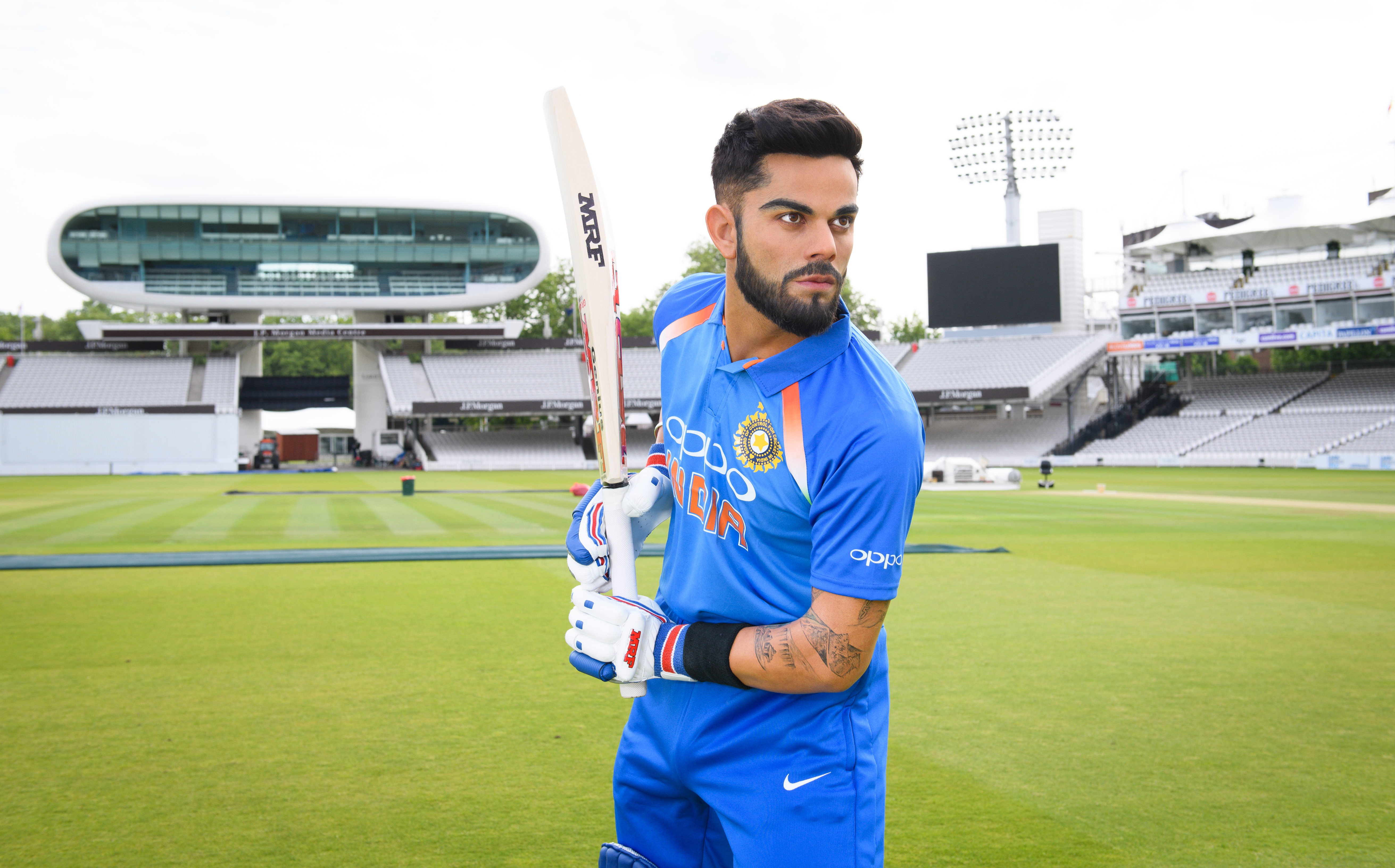 Cricket player Virat Kohli dressed in blue Indian cricket uniform